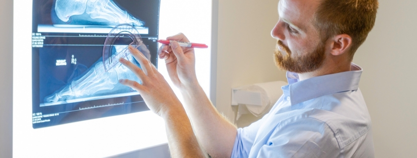 Podiatrist looking at xray machine with CPD techniques